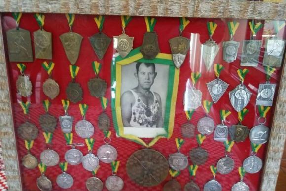 Ademir, filho de Adalberto, guarda as medalhas do pai em um quadroArquivo da família